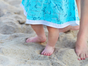Baby and mother's feet on the beach